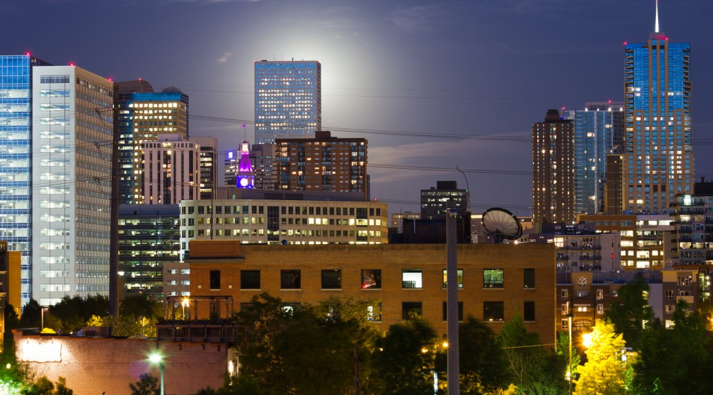 Glowing Moon Rises Behind The Denver CO Skyline